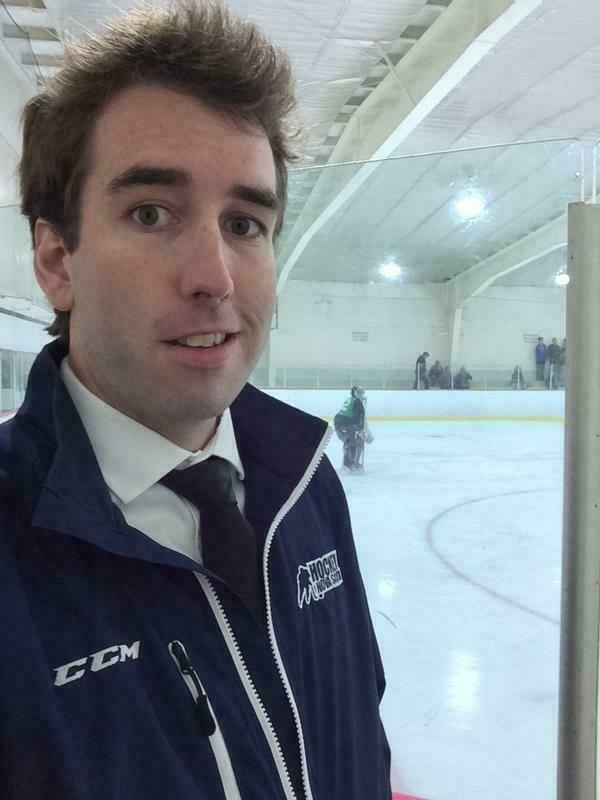 Me wearing a Hockey Nova Scotia jacket and a shirt and tie next to a rink.