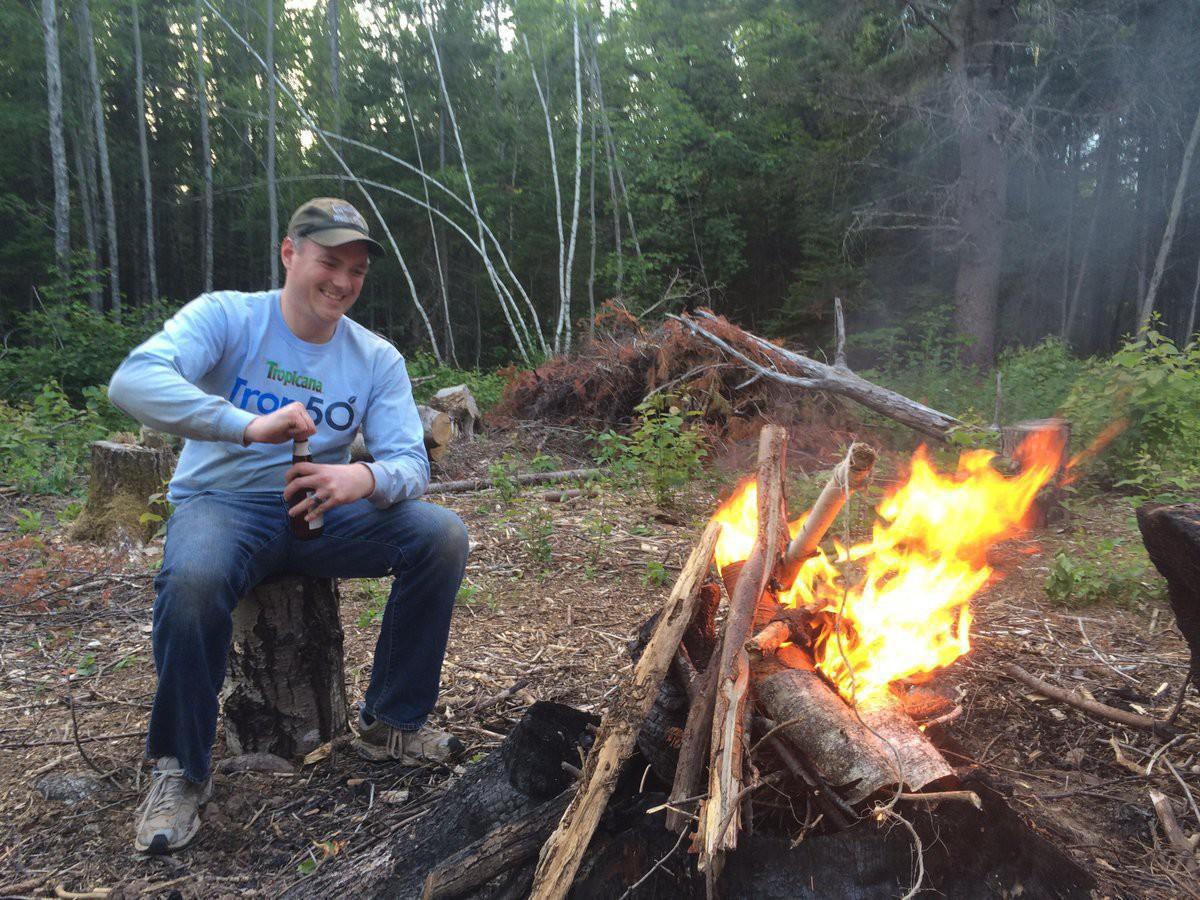 Mjke sitting next to a bon fire