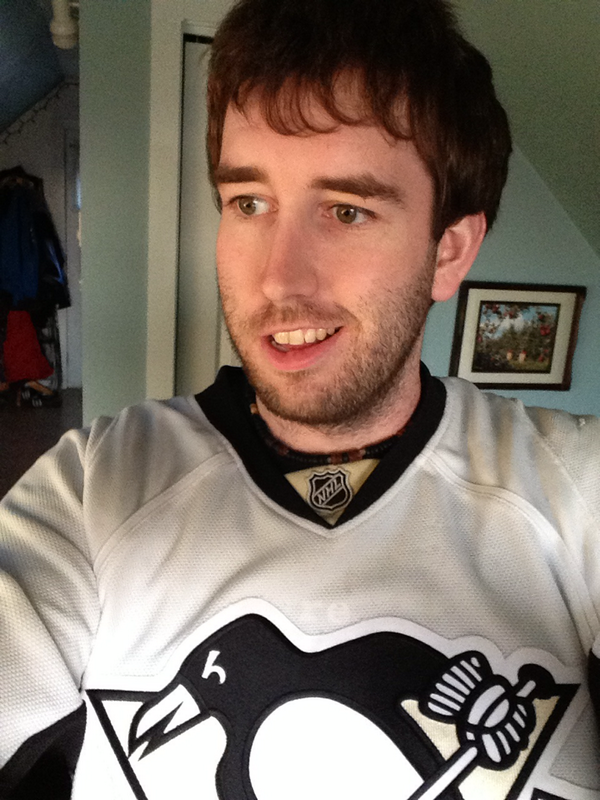 me wearing a Penguins jersey with the beginnings of a beard
