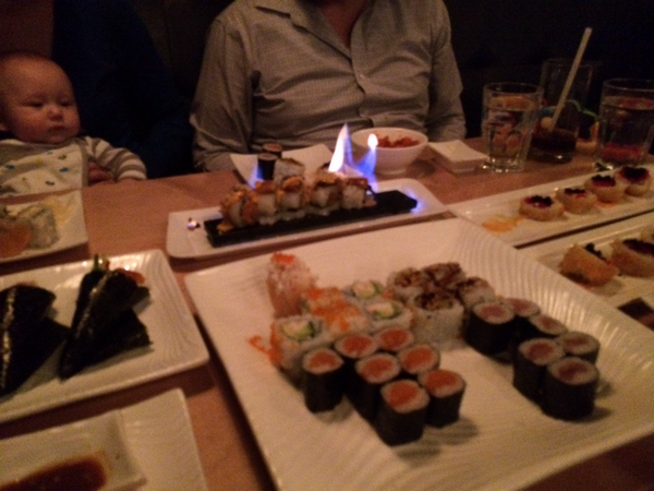 Many sushi rolls and one flaming tuna roll on fire