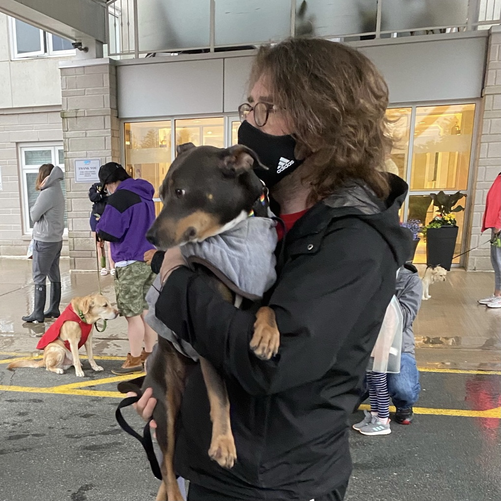 Luna being held in my arms while we stand with everyone and their dog outside our building