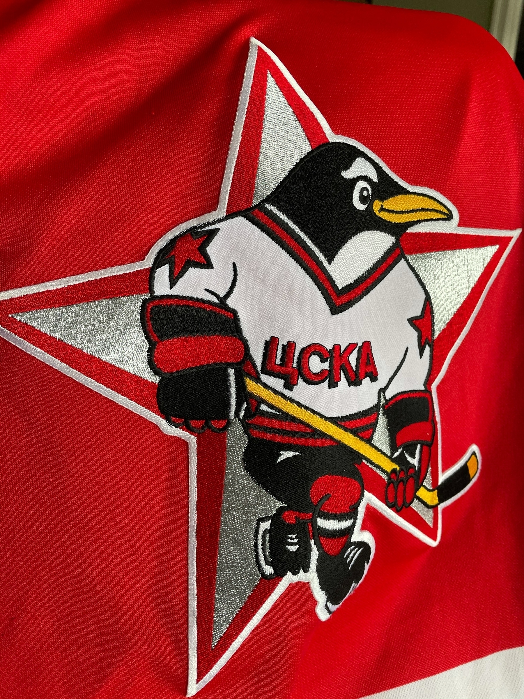 Russian Penguins jersey crest featuring a hockey playing penguin on a silver star